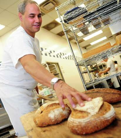 John Barricelli, owner of the SoNo Baking Company and Cafe, shows off some loaves of bread at his Norwalk shop.  He also has a second location in Westport. Photo: Autumn Driscoll / Connecticut Post