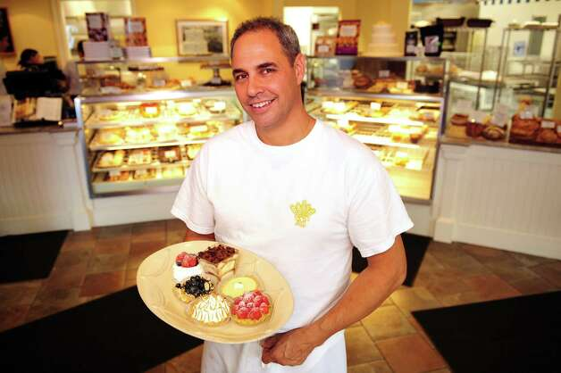 John Barricelli, owner of the SoNo Baking Company and Cafe, holds a plate of assorted pastries and tarts in his Norwalk shop.  He also has a second location in Westport. Photo: Autumn Driscoll / Connecticut Post