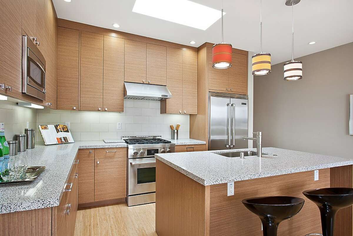 Both decorative and recessed lighting add ambiance to the kitchen, which also features custom cabinetry and stainless steel appliances.