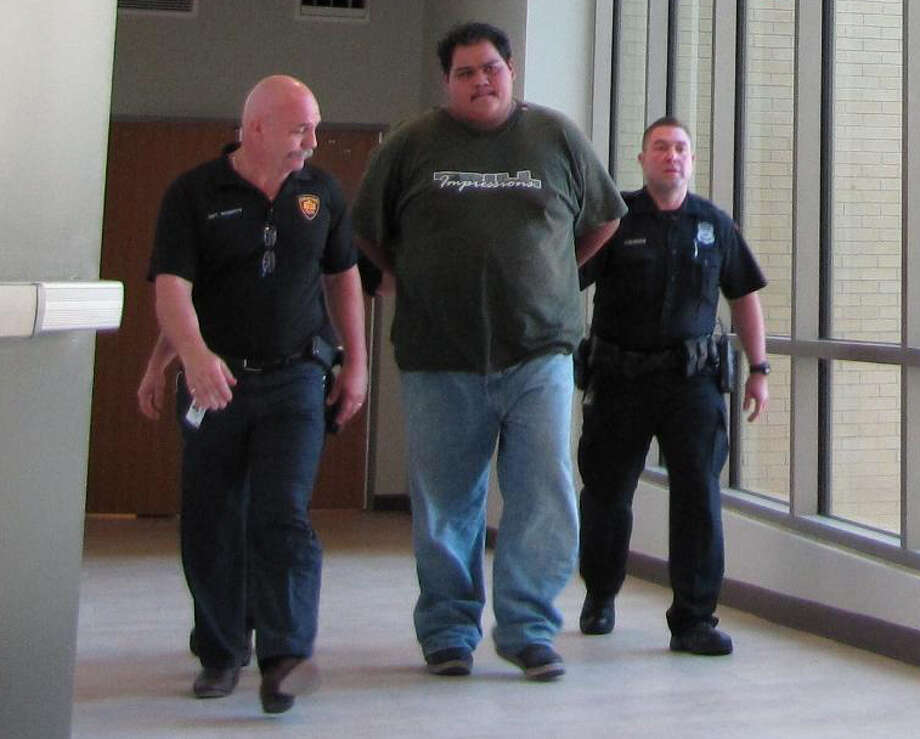 Police escort Bernardo Crisanto, 25, as he is transported to the county magistrate's office on Thursday, October 18, 2012. Crisanto was charged with murder in connection with the beating death of Juan Romero, 41.