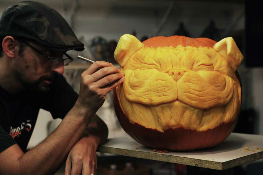 Alfred Paredes puts the finishing touches on a 3-D pumpkin sculpture for Halloween. Photo: --