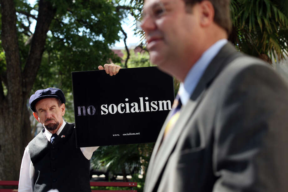"""Vladimir Lenin,"" holds a sign during an anti Pre-k 4 San Antonoi press conference in front of City Hall, Thursday, Oct. 18, 2012. In front of the podium is Jeff Judson, senior fellow at The Heartland Institute. Photo: Jerry Lara, San Antonio Express-News / © 2012 San Antonio Express-News"