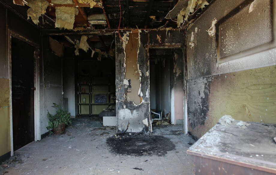 Seen through a broken window, this common room in the boarding home on Norfleet Street was burned during the fire that injured two residents. The blaze was believed to have been caused by a cigarette. Photo: Kin Man Hui, San Antonio Express-News / ©2012 San Antonio Express-News