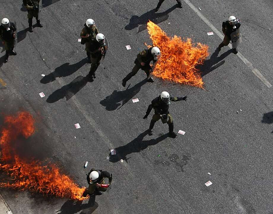 Protesters throw petrol bombs at riot police officers during a 24-hour nationwide general strike, Athens, Thursday, Oct. 18, 2012. Greece was facing its second general strike in a month Thursday as workers protested over another batch of austerity measures that are designed to prevent the bankruptcy of the country. (AP Photo/Thanassis Stavrakis) Photo: Thanassis Stavrakis, Associated Press