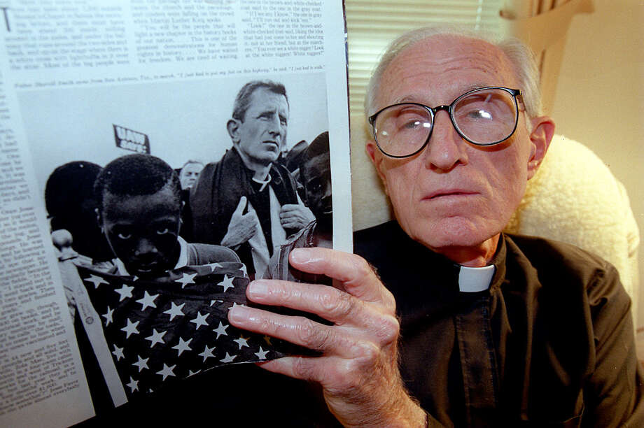 Father Sherrill Smith holds a Saturday Evening Post from 1965 with a photo of him in the Selma-to Montgomery march. Photo: MORRIS GOEN, Mg Father Sherrill Smith