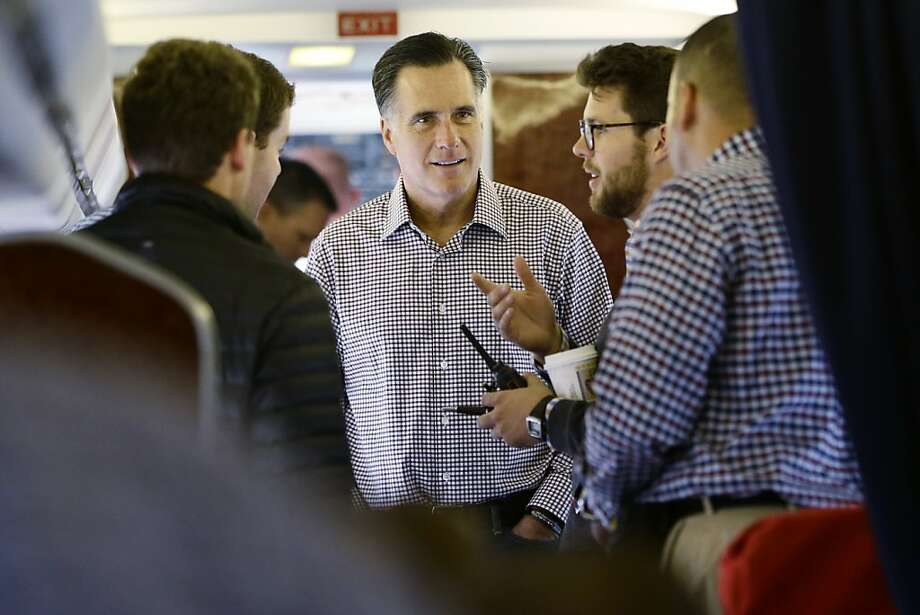 Mitt Romney confers with aide Charlie Pearce (second from right) on their plane in Sterling, Va. Photo: Charles Dharapak, Associated Press