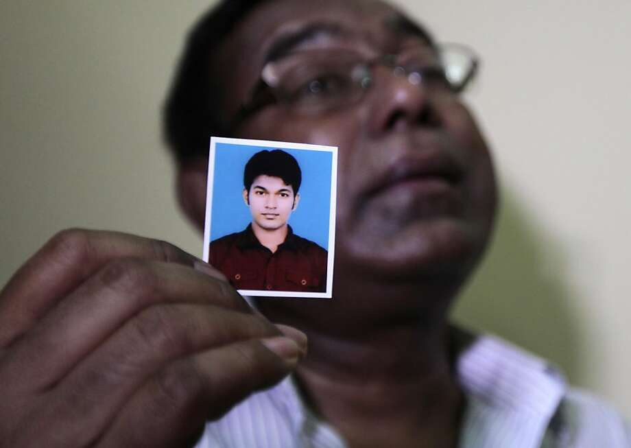Quazi Ahsanullah shows a photograph of his son Quazi Mohammad Rezwanul Ahsan Nafis. Photo: A.M.Ahad, Associated Press