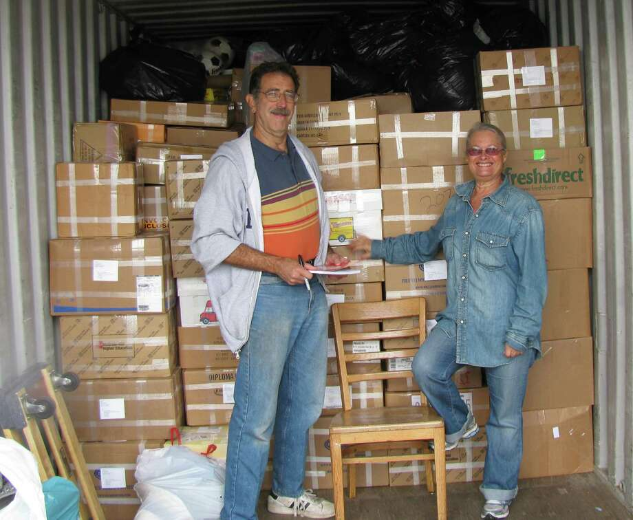 Mark Grashow, president of U.S.- Africa Children's Fellowship, left, stands with Relly Coleman, founder and president of Books for Zim, in front of over 1,600 pounds of books to be shipped to Zimbabwe. Photo: Contributed Photo