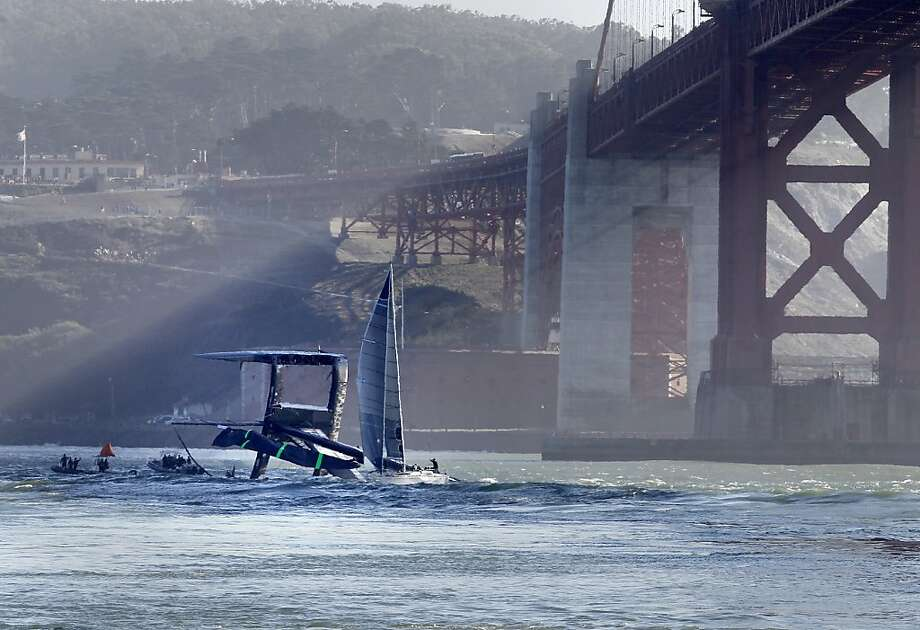 Oracle Team USA's catamaran capsizes in the bay during a training run for the America's Cup on Tuesday. Currents carried it to the ocean; luckily, no one was hurt. Photo: Brant Ward, Associated Press