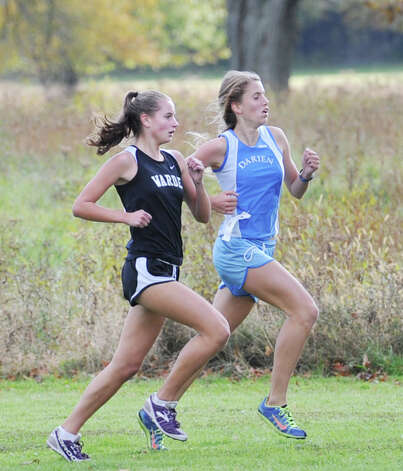 At left, Cate Allen of Fairfield-Warde High School goes stride for stride with Anne Johnston of Darien High School during the FCIAC girls high school cross country championship at Waveny Park in New Canaan, Thursday afternoon, Oct. 18, 2012. Allen finished first and Johnston placed fourth in the race. Photo: Bob Luckey / Greenwich Time