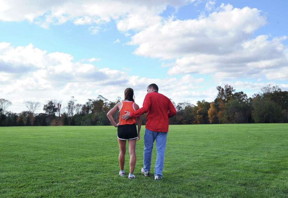 Jack Hergenrother puts his arm around his daughter Laura, a Ridgefield High School runner, after she finished sixth during the FCIAC girls high school cross country championship at Waveny Park in New Canaan, Thursday afternoon, Oct. 18, 2012. Photo: Bob Luckey / Greenwich Time