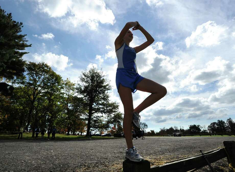 Darien High School runner Kaleigh Conway does a yoga-type relaxation exercise before the FCIAC girls high school cross country championship at Waveny Park in New Canaan, Thursday afternoon, Oct. 18, 2012. Photo: Bob Luckey / Greenwich Time