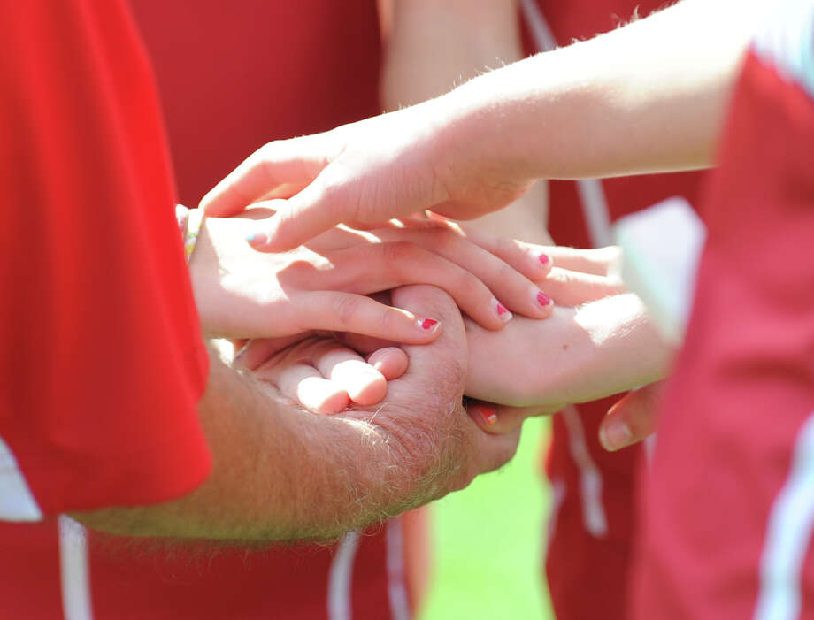 The Greenwich High School team puts their hands together prior to the start of the  FCIAC girls high school cross country championship at Waveny Park in New Canaan, Thursday afternoon, Oct. 18, 2012. Photo: Bob Luckey / Greenwich Time
