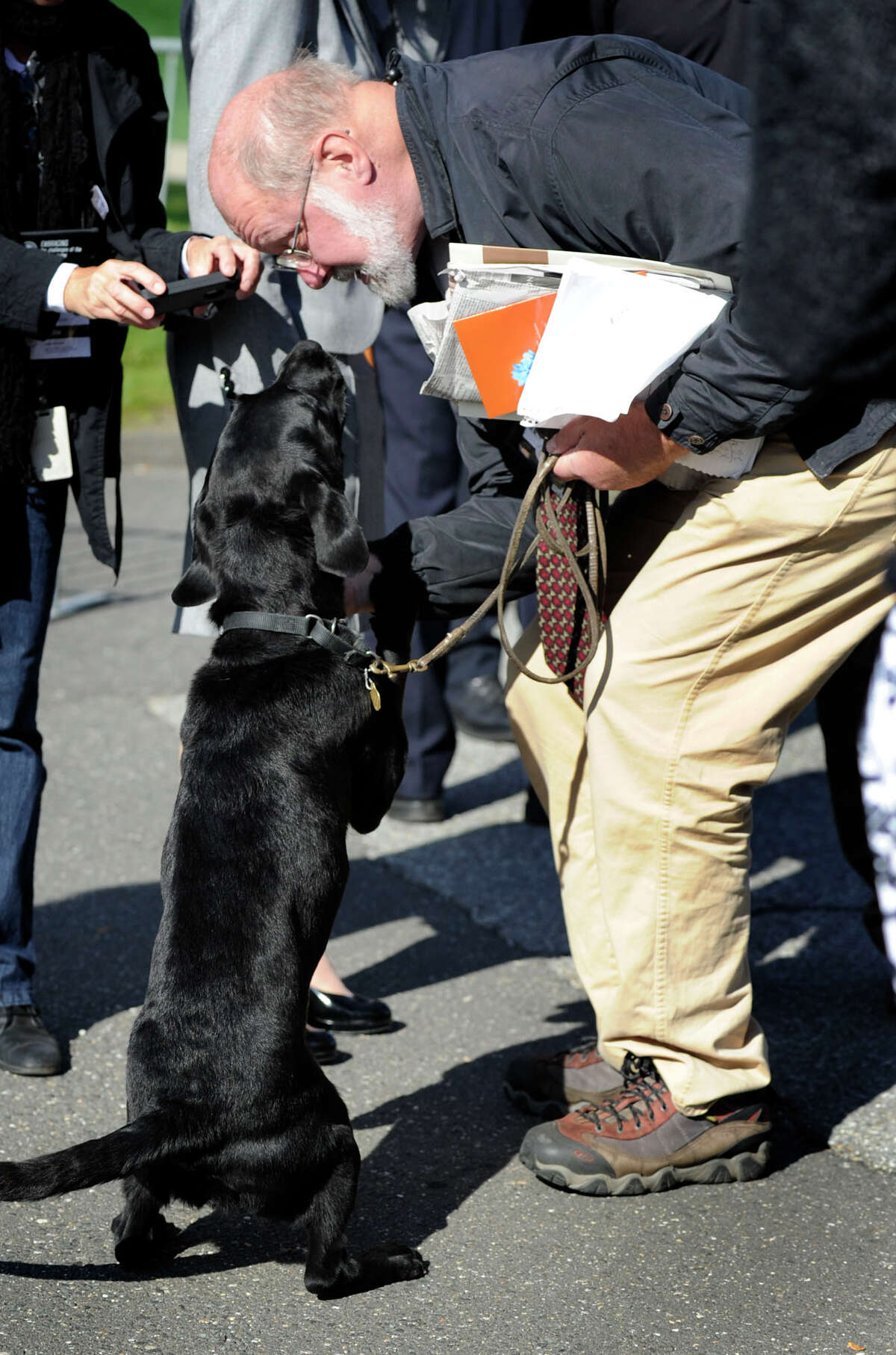 News-Times reporter Bob Miller, makes friends with a contraband-sniffing dog before a sweep of media and their equipment. A large turn out of media turned up at Western Connecticut State University to cover a visit by the Dalai Lama Thursday, Oct. 18, 2012.