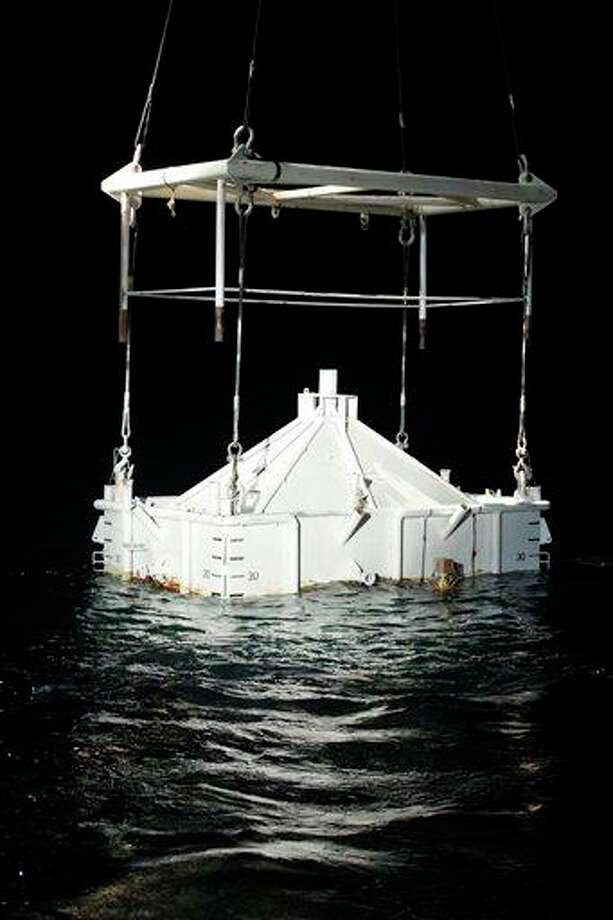 Officials say a containment device that was part of a failed attempt to stop the 2010 Gulf oil spill   shown here as crews were deploying it May 6, 2010 -- is leaking and is the source of an oil sheen discovered in the Gulf last month. Photo: Gerald Herbert, STF / AP