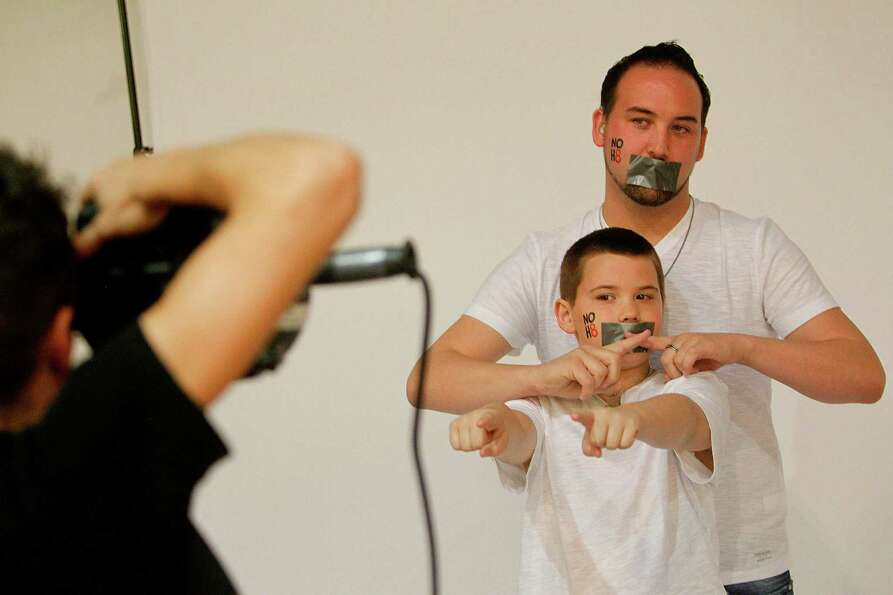 Jonathan Hendricks and son Ryan Hendricks, 11, participate in the NOH8