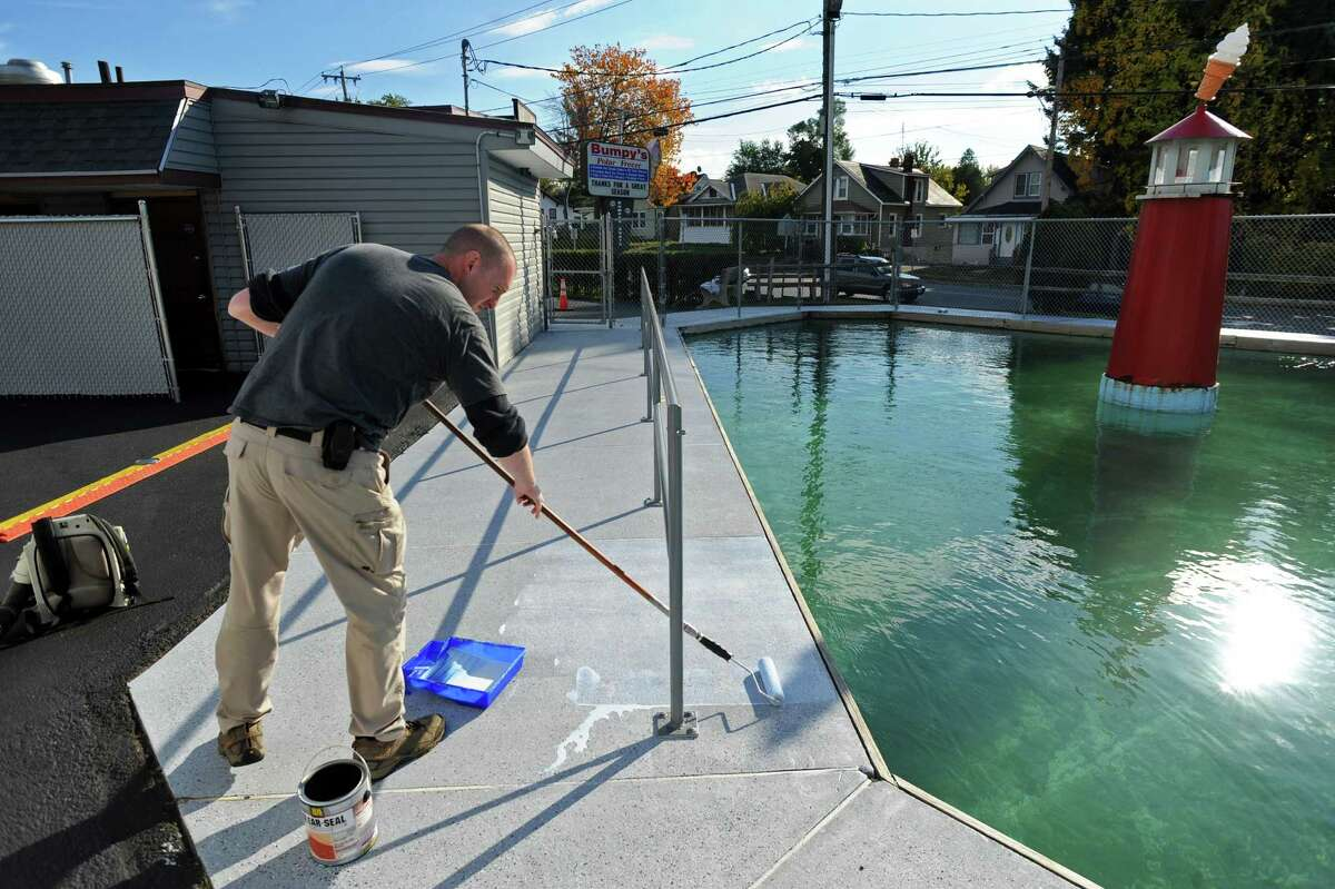 David Elmendorf and his wife just bought Bumpy's Polar Freeze, and are making improvement for next year's season, including resealing the deck of the Bumper Boats ride, on Thursday Oct. 18, 2012 in Schenectady, NY. (Philip Kamrass / Times Union)