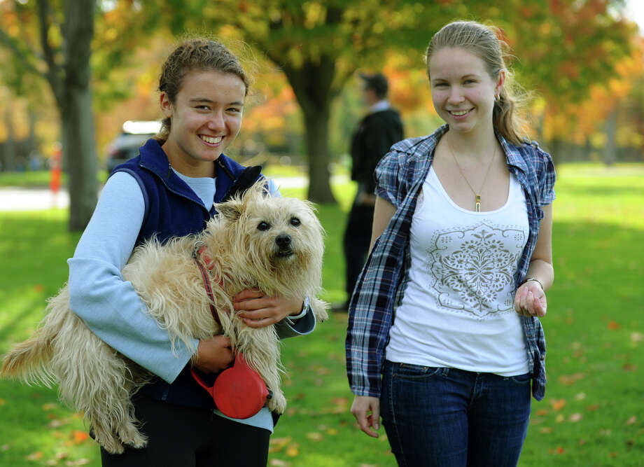 Former Wilton grad Rebecca Craig, left, hangs out to watch the boys FCIAC cross country action at Wavenly Park with her friend Nastia Biryuchinskaya and dog Tyke in New Canaan, Conn. on Thursday October 18, 2012. Photo: Christian Abraham / Connecticut Post