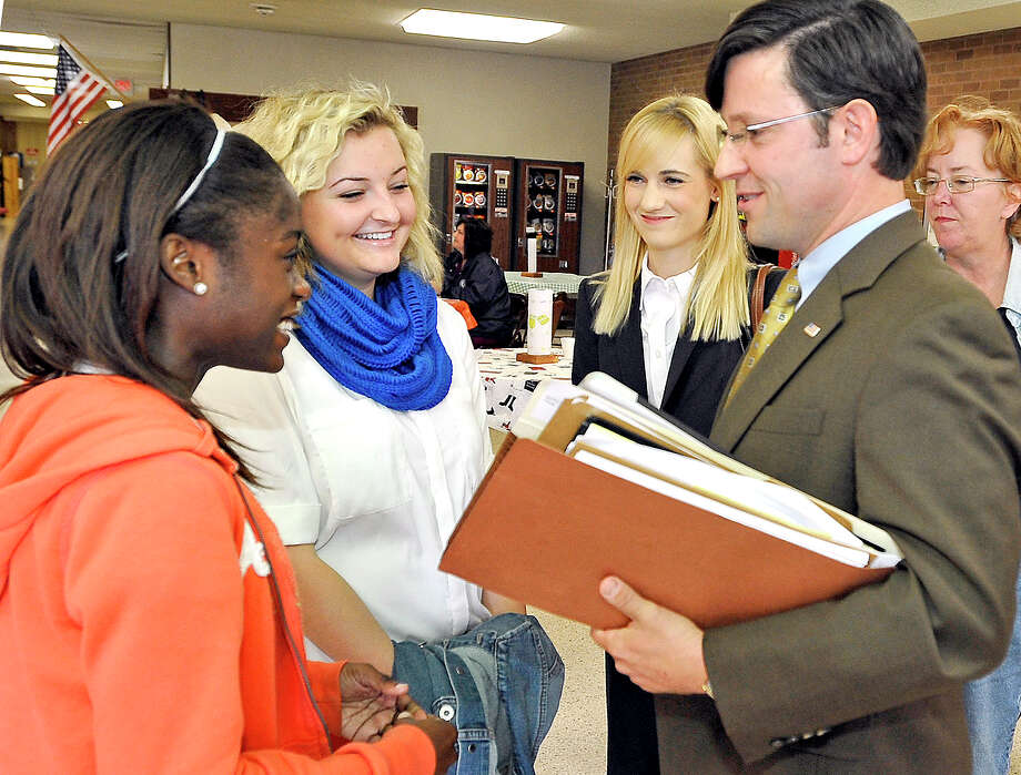 Liberty Institute attorney J. Michael Johnson had good news Thursday for Kountze High cheerleaders Kieara Moffett, left, and Rebekah Richardson after state District Judge Steve Thomas allowed the squad to continue displaying Bible banners at games. Photo: Dave Ryan