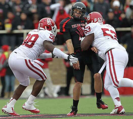 Texas Tech's Seth Doege is hit by Oklahoma's Casey Walker (53) as Chuka Ndulue (98) nears Doege during an NCAA college football game in Lubbock, Texas, Saturday, Oct. 6, 2012. (AP Photo/Lubbock Avalanche-Journal, Stephen Spillman) LOCAL TV OUT Photo: Stephen Spillman, Associated Press / Lubbock Avalanche-Journal
