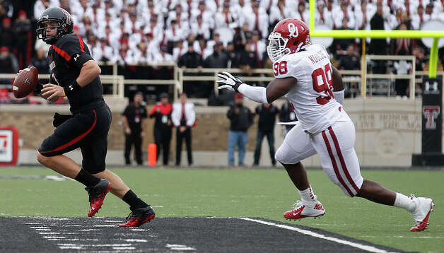 Texas Tech's Seth Doege tries to get away from Oklahoma's Chuka Ndulue during an NCAA college football game in Lubbock, Texas, Saturday, Oct. 6, 2012. (AP Photo/Lubbock Avalanche-Journal, Stephen Spillman) LOCAL TV OUT Photo: Stephen Spillman, Associated Press / Lubbock Avalanche-Journal