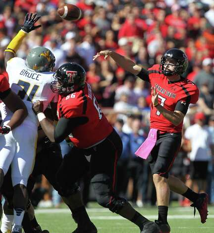 Texas Tech's Seth Doege throws over West Virginia's Isaiah Bruce while getting a block from Deveric Gallington (66) during their NCAA college football game in Lubbock, Texas, Saturday, Oct. 13, 2012. (AP Photo/Lubbock Avalanche-Journal, Stephen Spillman) Photo: Stephen Spillman, Associated Press / Lubbock Avalanche-Journal