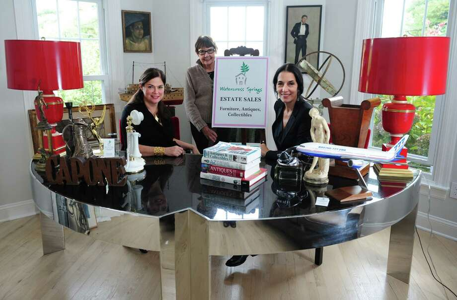 Partners Angela Capone, left, and Lisa Capone, of Watercress Springs Estate Sales, sit behind the desk in their Fairfield office with their mother, Marge Capone, 20 year owner of Watercress Springs Antiques who inspired their current business. Photo: Autumn Driscoll / Connecticut Post