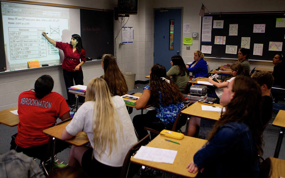 "Students watch as teacher Leticia Allred explains a lecture during a pre ap geometry class at Clear Brook High School Tuesday, Oct. 16, 2012, in Friendswood. Clear Brook High School is one of a growing number who has started to use ""flipped teaching"" - an approach in which students view lectures at home and do homework in school. (Cody Duty / Houston Chronicle) Photo: Cody Duty / © 2012 Houston Chronicle"