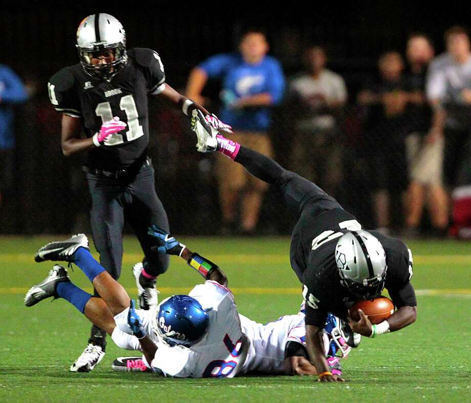 Clear Brook High school running back Kameron Smith (15)  leaps over  two Dickinson Gator defenders as teammate Chase Cyprien (11) comes to block in the first half of Dickinson High school and Clear Brook High school's match up at CCISD Veterans Memorial Stadium, Thursday, Oct. 18, 2012, in League City. Photo: Billy Smith II, Houston Chronicle / © 2012 Houston Chronicle