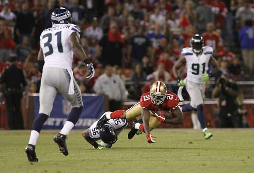 Running back Frank Gore (21) gets brought down by Seattle Seahawks linebacker Leroy Hill (56) during the San Francisco 49ers game against the Seattle Seahawks at Candlestick Park in San Francisco, Calif., on Thursday October 18, 2012. Photo: Stephen Lam, Special To The Chronicle