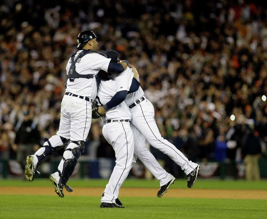 From left, Detroit Tigers' Gerald Laird, Phil Coke and Jhonny Peralta celebrate after winning Game 4 of the American League championship series 8-1, against the New York Yankees, Thursday, Oct. 18, 2012, in Detroit. The Tigers move on to the World Series. (AP Photo/Paul Sancya ) Photo: Paul Sancya