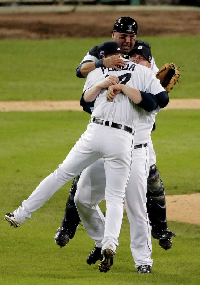 Detroit Tigers' Gerald Laird, rear, Phil Coke, center and Jhonny Peralta (27)celebrate after winning Game 4 of the American League championship series against the New York Yankees Thursday, Oct. 18, 2012, in Detroit. The Tigers move on to the World Series. (AP Photo/Charlie Riedel) Photo: Charlie Riedel