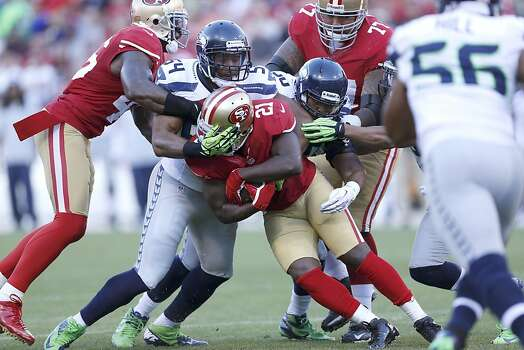 Seattle defense attempts to take down 49ers Running back Frank Gore (21)  during the first quarter the San Francisco 49ers game against the Seattle Seahawks at Candlestick Park in San Francisco, Calif., on Thursday October 18, 2012. Photo: Beck Diefenbach, Special To The Chronicle