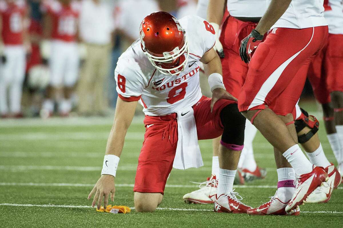 Houston quarterback David Piland (8) is slow to get up after being knocked out of the game by a late hit from Southern Methodist linebacker Taylor Reed (44) during the second quarter of an NCAA college football game at Ford Stadium, Thursday, Oct. 18, 2012, in Dallas.
