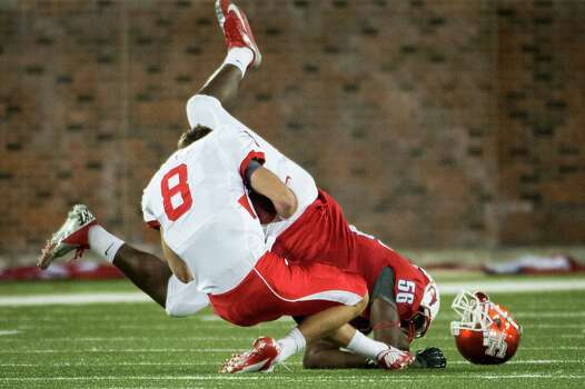 Houston quarterback David Piland (8) had his helmet knocked off as he is dropped for a loss by Southern Methodist linebacker Ja'Gared Davis (56) during the second quarter of an NCAA college football game at Ford Stadium, Thursday, Oct. 18, 2012, in Dallas. Photo: Smiley N. Pool, Houston Chronicle / © 2012  Houston Chronicle