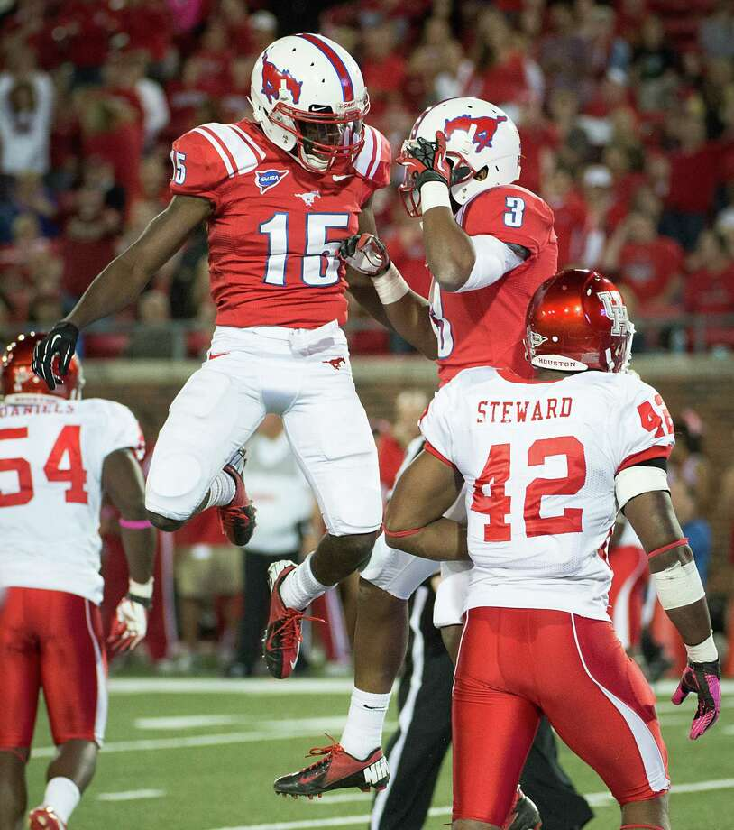 Southern Methodist wide receiver Jeremy Johnson (15) and wide receiver Darius Johnson (3) celebrate in front of Houston linebacker Phillip Steward (42) during the second quarter of an NCAA college football game at Ford Stadium, Thursday, Oct. 18, 2012, in Dallas. Photo: Smiley N. Pool, Houston Chronicle / © 2012  Houston Chronicle