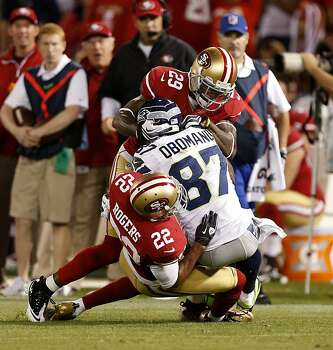 San Francisco 49ers cornerbacks Chris Culliver (29, top) and Carlos Rogers (22) push back Seattle Seahawks wide receiver Ben Obomanu (87) during the fourth quarter of their NFL game at Candlestick Park on Thursday, October 18, 2012 in San Francisco, Calif. Photo: Beck Diefenbach, Special To The Chronicle