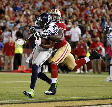 San Francisco 49ers tight end Vernon Davis (85, right) tackles Seattle Seahawks cornerback Brandon Browner after Browner intercepted the ball in the enzone during the fourth quarter of their NFL game at Candlestick Park on Thursday, October 18, 2012 in San Francisco, Calif. Photo: Beck Diefenbach, Special To The Chronicle