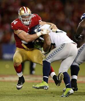 San Francisco 49ers defensive tackle Justin Smith (94, left) tackles Seattle Seahawks running back Marshawn Lynch (24) during the fourth quarter of their NFL game at Candlestick Park on Thursday, October 18, 2012 in San Francisco, Calif. Photo: Beck Diefenbach, Special To The Chronicle