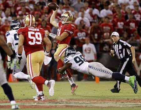 Alex Smith slips out of a tackle and throws the ball away. The San Francisco 49ers took on the Seattle Seahawks on Thursday, October 18, 2012. Photo: Sean Culligan, SFC