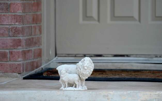 A lion and lamb figurine is placed by the front door where Tim and Iliana Archuleta, as well as Rogelio Archuleta and three adoptive and two biological children lived in the 7900 block of Oak Pointe. Rogelio Archuleta, uncle of the children, has been charged with three counts of causing serious bodily injury to the adoptive children. Oct. 18, 2012. Photo: Billy Calzada, San Antonio Express-News / © 2012 San Antonio Express-News