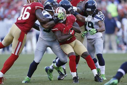 Seattle defense attempts to take down 49ers running back Frank Gore (21)  during the first quarter of the San Francisco 49ers game against the Seattle Seahawks at Candlestick Park in San Francisco, Calif., on Thursday October 18, 2012. Photo: Beck Diefenbach, Special To The Chronicle