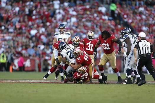 49ers Defensive tackle Justin Smith (94), Linebacker NaVorro Bowman (53, Linebacker Aldon Smith (99) and Safety Dashon Goldson (38) bring down Seattle Seahawks running back Marshawn Lynch (24) during his first play as a Seahawk. The San Francisco 49ers played the Seattle Seahawks at Candlestick Park in San Francisco, Calif., on Thursday October 18, 2012. Photo: Beck Diefenbach, Special To The Chronicle