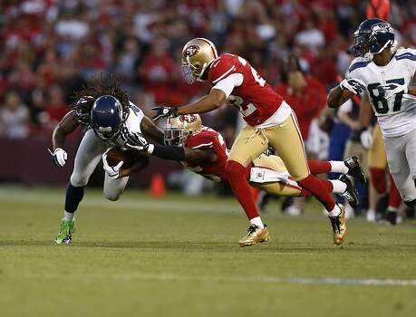 Seattle Seahawks wide receiver Sidney Rice (18) is brought down by Cornerback Tarell Brown (25) and Cornerback Carlos Rogers (22) during the first half of the San Francisco 49ers game against the Seattle Seahawks at Candlestick Park in San Francisco, Calif., on Thursday October 18, 2012. Photo: Beck Diefenbach, Special To The Chronicle