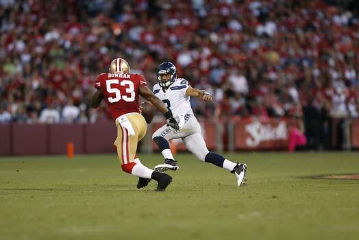 Seattle Seahawks quarterback Russell Wilson (3) looks to run pass Linebacker NaVorro Bowman (53) during the first half of the San Francisco 49ers game against the Seattle Seahawks at Candlestick Park in San Francisco, Calif., on Thursday October 18, 2012. Photo: Beck Diefenbach, Special To The Chronicle