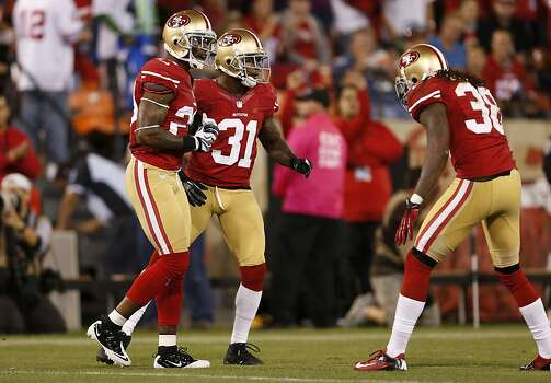Cornerback Chris Culliver (29), Safety Donte Whitner (31) and Safety Dashon Goldson (38) celebrate after a play in the first half of the San Francisco 49ers game against the Seattle Seahawks at Candlestick Park in San Francisco, Calif., on Thursday October 18, 2012. Photo: Beck Diefenbach, Special To The Chronicle