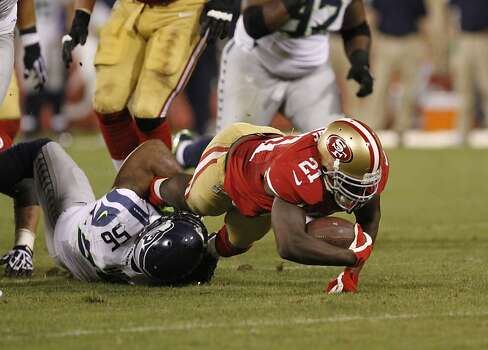 Running back Frank Gore (21) is taken down by Seattle Seahawks linebacker Leroy Hill (56) during the San Francisco 49ers game against the Seattle Seahawks at Candlestick Park in San Francisco, Calif., on Thursday October 18, 2012. Photo: Stephen Lam, Special To The Chronicle