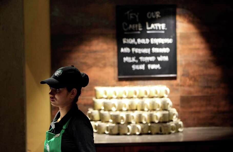 An Indian employee gets ready to start the latte habit in India. (AP Photo/Rajanish Kakade)