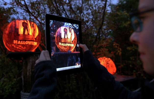 "A girl uses her iPad to photograph a pumpkin carved with the theme of the movie ""Halloween"" while viewing illuminated jack o' lanterns at the Roger Williams Park Zoo in Providence, R.I., Monday, Oct. 8, 2012. Some 5,000 carved pumpkins are on display for this year's Jack-o'-lantern Spectacular, one of the nation's largest jack-o'-lantern shows. (AP Photo/Charles Krupa) Photo: Charles Krupa, Associated Press / AP"