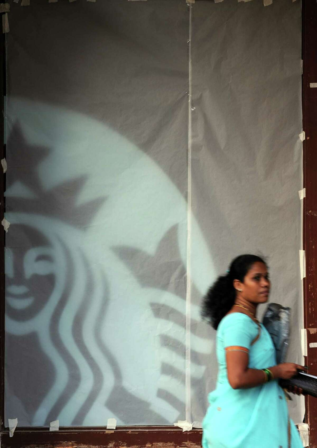 A pedestrian walks past a window, covered with translucent material, of Starbucks Mumbai store ( INDRANIL MUKHERJEE/AFP/Getty Images)